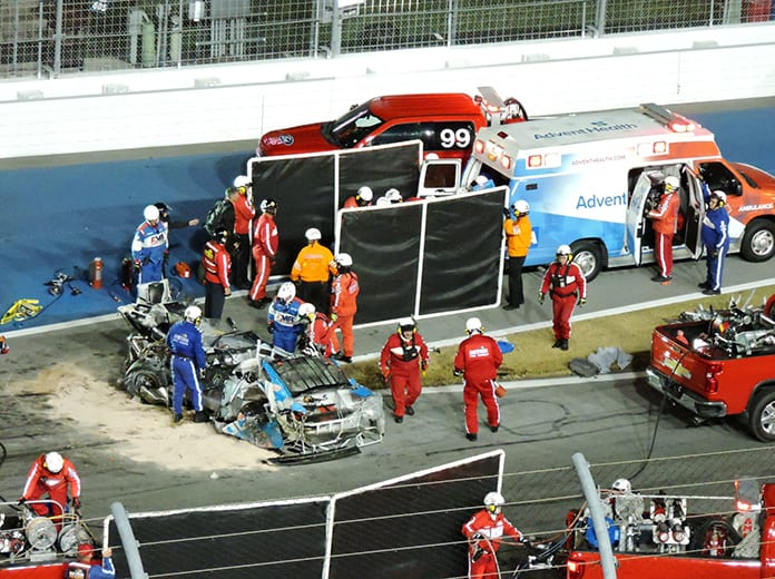 Safety workers surround the damaged remains of Ryan Newman's race car following the last-lap crash in the Daytona 500 last Monday. (Paul Anton Photo)