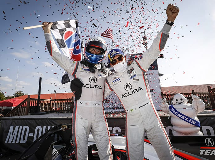Ricky Taylor (left) and Helio Castroneves celebrate after winning Sunday's IMSA WeatherTech SportsCar Championship event at the Mid-Ohio Sports Car Course. (IMSA Photo)