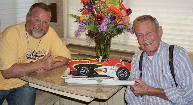 SPEED SPORT writer Bruce Martin (left) with the late Bobby Unser in 2018. Borg Warner sent this special cake when Unser arrived at Indianapolis Motor Speedway in May of 2018 to celebrate the 50th anniversary of his first Indianapolis 500 victory in 1968. (Bruce Martin Collection)